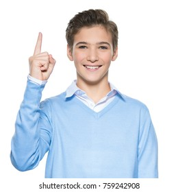Portrait of cheerful teen boy with good idea -  isolated over white background. Young guy points up by finger