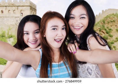 Portrait of cheerful teenage girls using a smartphone to take a selfie on the Great Wall of China
