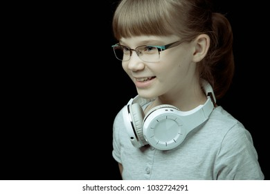 Portrait of a cheerful teenager girl in glasses with white headphones on her neck