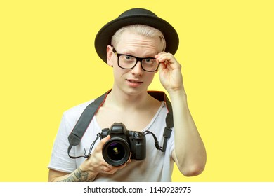 Portrait of cheerful traveler bloger with camera and fixing spectacles with hands preparing to make a shot. Blond man dressed in casual white t-shirt and black hat. Isolated over yellow background