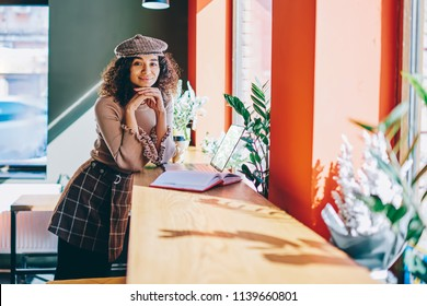 Portrait of cheerful trendy hipster girl standing near table with laptop device and textbook on enjoying leisure, smiling female freelancer looking at camera after e learning at coworking space