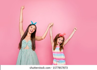 Portrait of cheerful two women holding hands wearing headbands dress skirt isolated over pink background