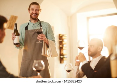 Portrait of cheerful waiter bringing bottle of wine at vineyard restaurant lit by sunlight, copy space