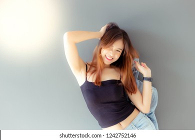 Portrait cheerful woman. Attractive beautiful woman gets happiness with smile face. Charming beautiful young lady wears jeans, camisole and holding denim denim jacket. Cool girl has nice skin and body