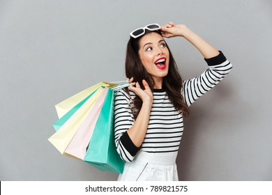 Portrait of a cheerful woman holding shopping bags and looking away isolated over gray background