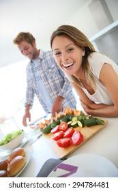 Portrait of cheerful woman in kitchen, boyfriend preparing lunch