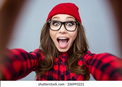 Portrait of a cheerful woman making selfie photo over gray background