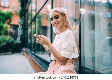 Portrait of cheerful woman with mobile phone in hands resting on urban setting with public internet connection, happy millennial hipster girl smiling at camera,concept of generation and digitalisation