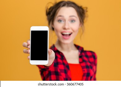 Portrait of a cheerful woman showing blank smartphone screen over yellow background. Focus on smartphone