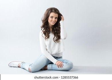 Portrait of a cheerful woman sitting on the floor on gray background. Girl with long wavy hair.