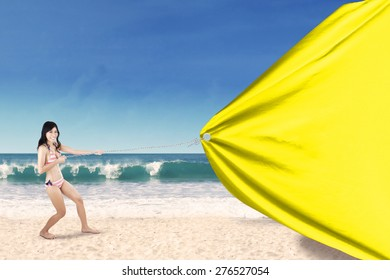 Portrait of cheerful woman wearing swimsuit on the coast while pulling a blank banner