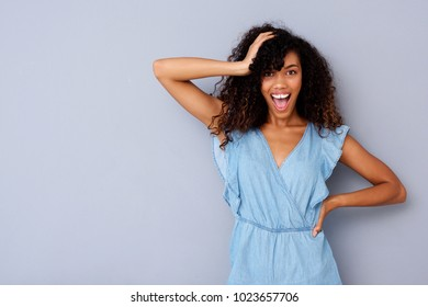 Portrait of cheerful young african american woman laughing against gray wall