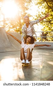 Portrait of a cheerful young african couple with skateboards having fun together at the skate park
