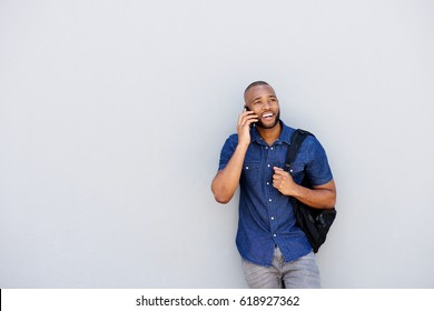 Portrait of cheerful young african guy talking on cell phone against gray background