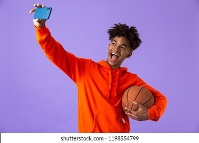 Portrait of a cheerful young african man holding a basketball isolated over violet background, takign a selfie