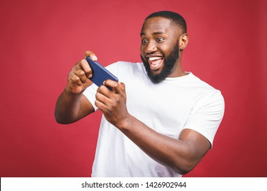 Portrait of a cheerful young african man dressed in casual playing games on mobile phone isolated over red background.