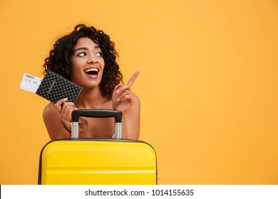 Portrait of a cheerful young african woman dressed in summer clothes holding passport with flying tickets while standing with a suitcase and pointing finger away isolated over yellow background
