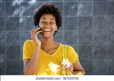Portrait of a cheerful young african woman standing outdoors and making a phone call