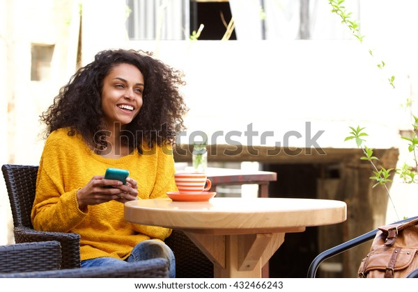 Portrait of cheerful young african woman sitting at outdoor cafe with a cell phone