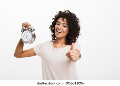 Portrait of cheerful young afro american woman holding alarm clock and showing thumbs up isolated over white background