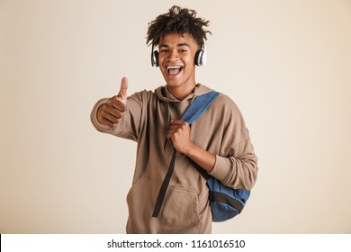 Portrait of a cheerful young afro american man dressed in hoodie with headphones carrying backpack isolated, showing thumbs up