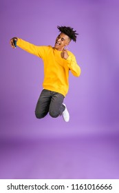 Portrait of a cheerful young afro american man dressed in sweatshirt taking a selfie while jumping isolated