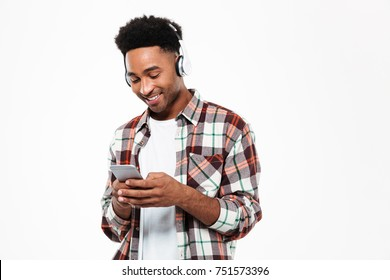 Portrait of a cheerful young afro american man in headphones standing and messaging on mobile phone isolated over white background
