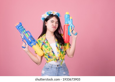Portrait cheerful young asian woman holding plastic water gun Smiling and having fun playing in the water Songkran festival, Thailand. isolated on pink background. Thai New Year's Day.