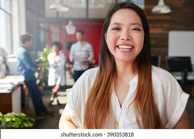Portrait of cheerful young asian woman standing in office with coworkers talking in background. Female creative professional looking at camera and smiling.