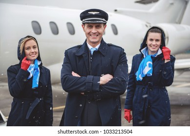 Portrait of cheerful young aviator and happy stewardess looking at camera opposite plane. Occupation concept