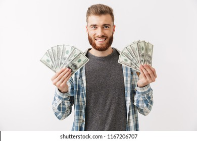 Portrait of a cheerful young bearded man standing isolated over white, showing money banknotes
