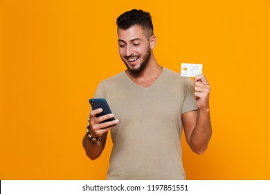 Portrait of a cheerful young bearded man in t-shirt isolated over orange background, holding mobile phone, showing plastic credit card