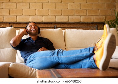 Portrait of cheerful young black man lying on sofa with headphones and listening to music