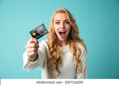 Portrait of a cheerful young blonde woman in sweater showing credit card isolated over blue background