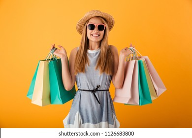 Portrait of a cheerful young blonde woman in summer hat and sunglasses holding shopping bags isolated over yellow background
