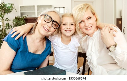 Portrait of cheerful young blonde woman with her dearest mother and daughter in a living room