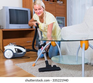 Portrait of cheerful young blonde woman vacuuming in living room