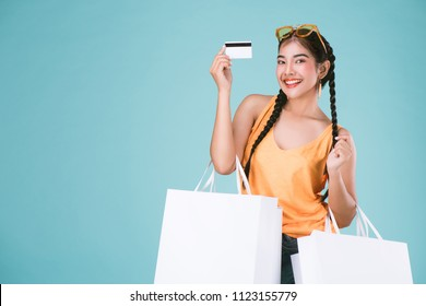 portrait of cheerful young brunette woman holding credit card and shopping bags over Blue background.