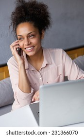 Portrait of a cheerful young business woman talking on mobile phone with laptop