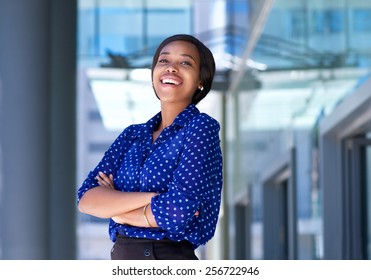Portrait of a cheerful young business woman laughing outside office building