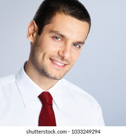 Portrait of cheerful young businessman, against grey background