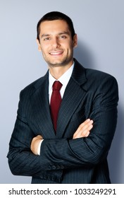 Portrait of cheerful young businessman with crossed arms pose, against grey background