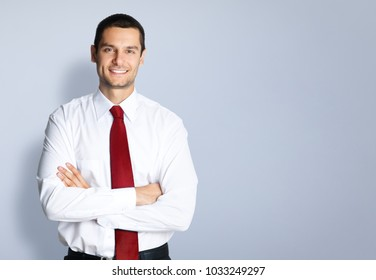 Portrait of cheerful young businessman with crossed arms pose, with blank copyspace area for text or slogan, against grey background
