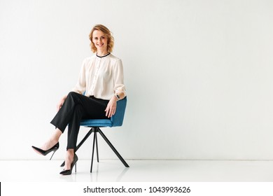 Portrait of a cheerful young businesswoman sitting in a chair against white background