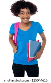 Portrait of a cheerful young college student in trendy wear. Holding back pack, book and clipboard.