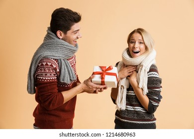 Portrait of a cheerful young couple dressed in sweaters and scarves standing isolated over beige backgorund, happy man giving his girlfriend a present