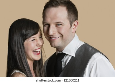 Portrait of cheerful young couple over colored background