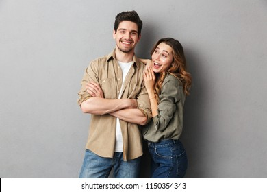 Portrait of a cheerful young couple standing together isolated over gray background, laughing