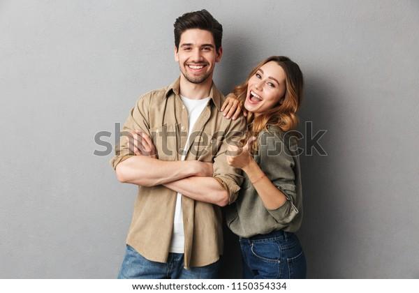 グレイの背景に明るい若い夫婦のポートレート、親指を示す