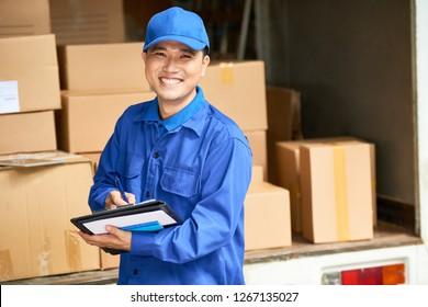 Portrait of cheerful young delivery man with digital tablet smiling at camera